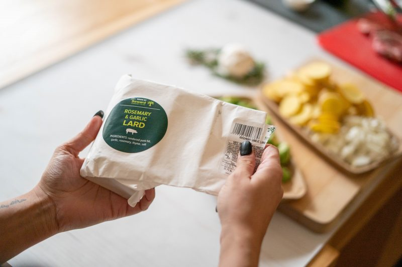 someone's hands pictured opening a package of Seward-made Rosemary and Garlic Flavored Lard