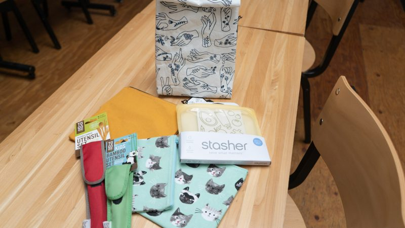 lunch bag, reusable utensils, and washable snack bags on a long wooden table