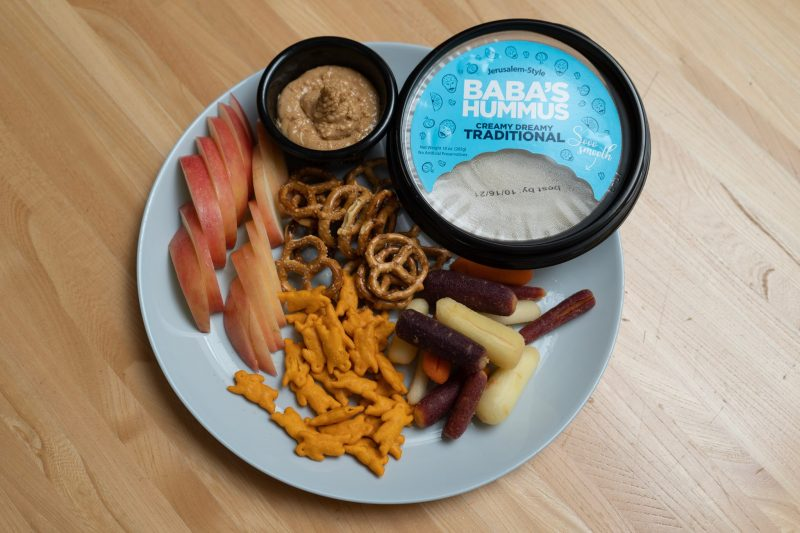 plate full of snacks including hummus, peanut butter, sliced apple, baby carrots, pretzels, and cheddar crackers