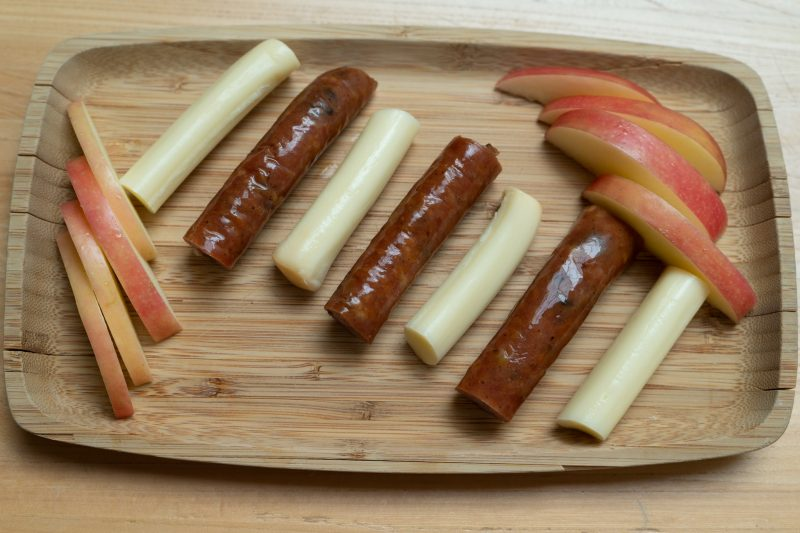 apple slices, sausage, and string cheese on a wooden plate for snacking