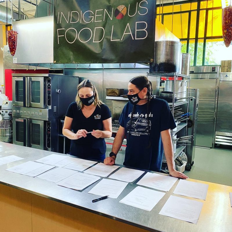 """two people planning in a kitchen under an """"indigenous food lab"""" banner"""
