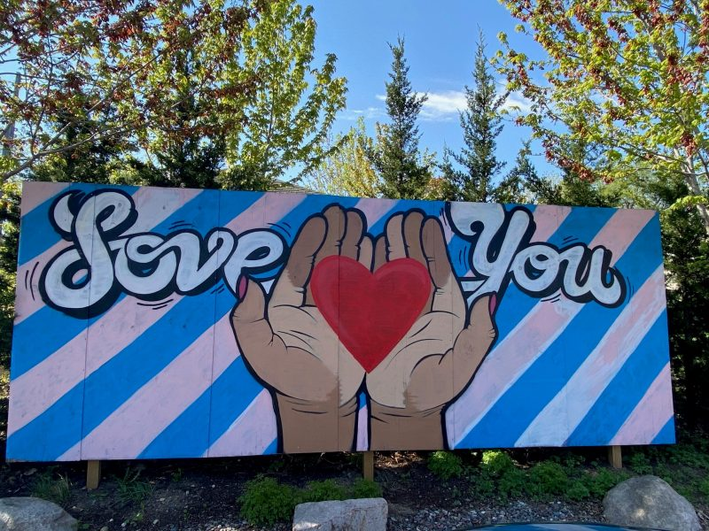 painting of hands of varying skin tones holding a heart that says