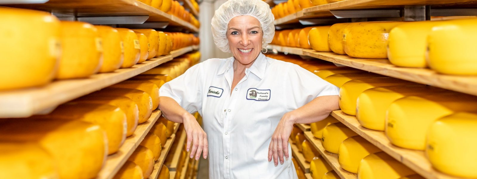 woman grinning surrounded by bright orange wheels of aging cheese