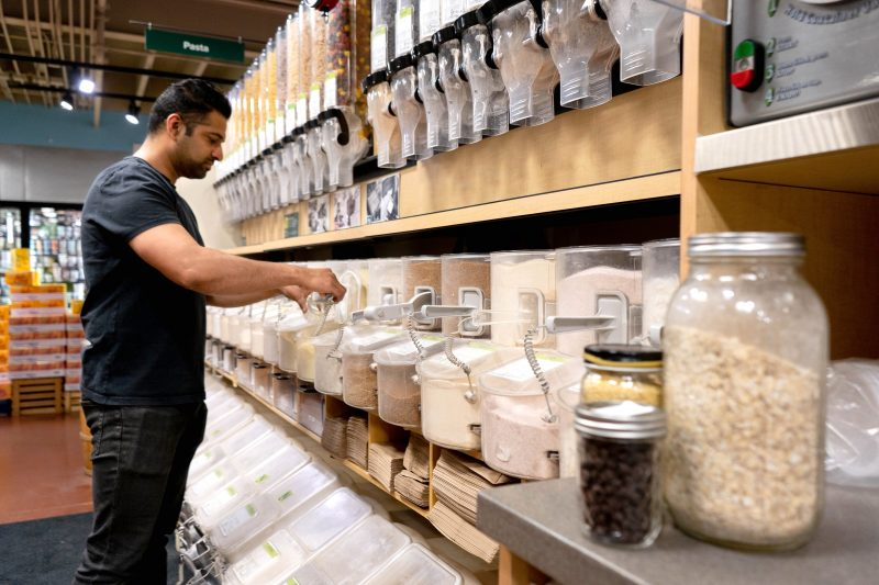 person standing in bulk aisle scooping in a bulk bin with glass jars in the foreground