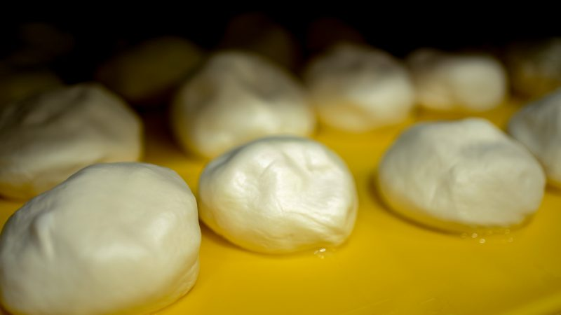 fresh mozzarella balls on a yellow pan drying