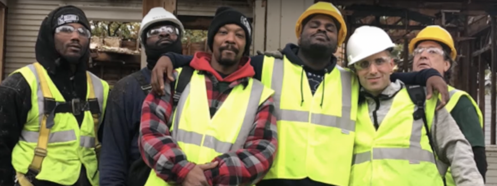 group of men in high-visibility vests and hardhats gathered together with arms around one another