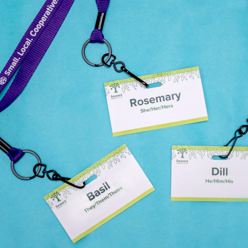 Three Seward Co-op nametags each with different pronouns displayed (she/her, he/him, they/them)